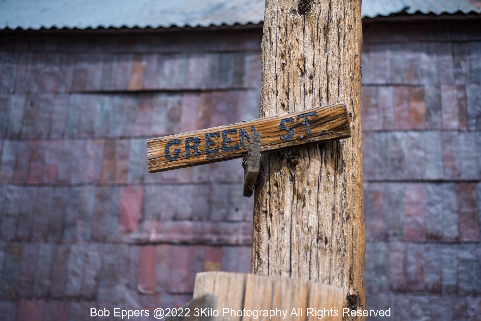 Photo of the Green Street Sign in Bodie, CA.  The shingles in the background are flattened out food cans and are over 100 years old.