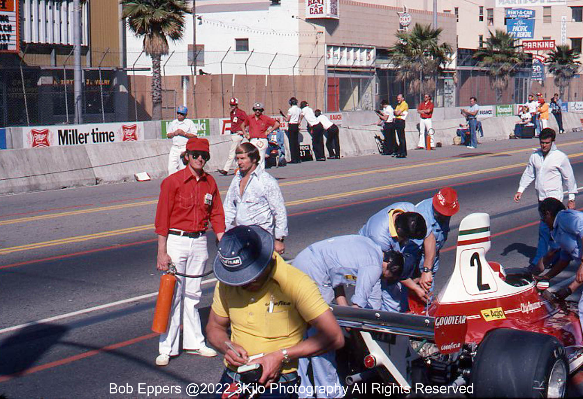 Photo of Parnelli Jones and Al Unser in the pit lane..  3 Kilo is in the red shirt holding the fire extinguisher.  1976
